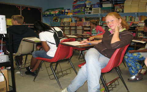 A female teenage student with straight ginger hair smiles at the camera while her peers work on an assignment in their classroom.