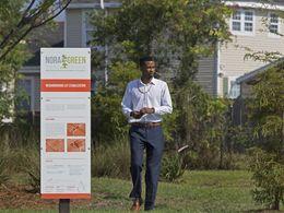 Brandon Rapp (G.N.O.–LAD '12), Economic Development Fellow, Greater New Orleans, Inc walks in rain garden in New Orleans' Filmore neighborhood.