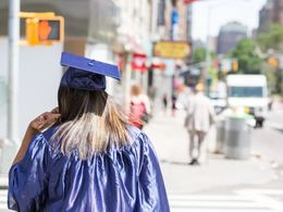 A student walking down the street wearing a graduation cap and gown.