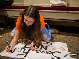 A student prepares her poster for a march on gun safety.