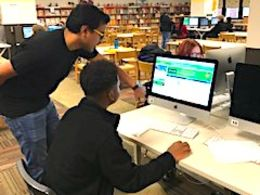 A teacher helps a student learn how to code.