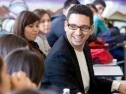 A young teacher with short black hair, black framed glasses and a black blazer smiling in the middle of a room full of students