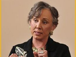 A middle-aged woman with short curly gray hair, wearing gold earrings a gold necklace with charms, and a black blazer with a white embroidered plant motif, with arms bent up at the elbows.
