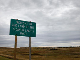"""A green highway sign that reads, """"Welcome to the Land of the Sicangu Lakota Oyate;"""" a field and blue sky is off in the distance."""
