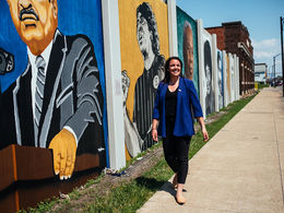 A woman walking in front of murals