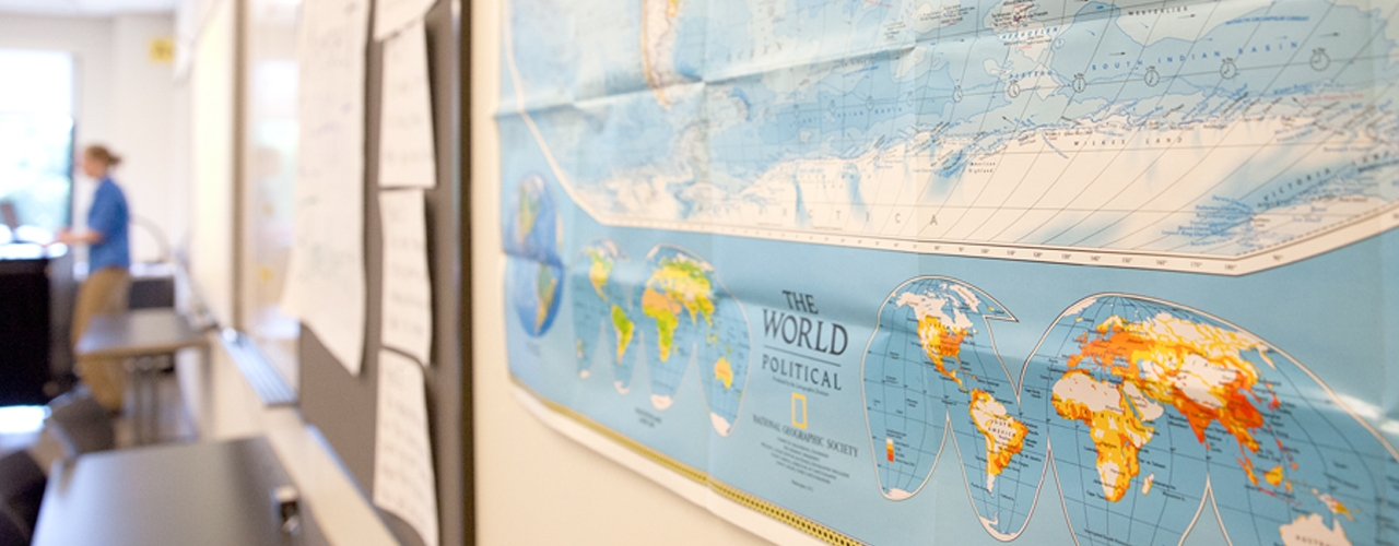 Image of class room with a world map on the wall.