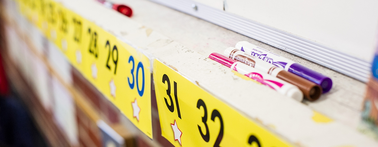 Image of stationery supplies arranged on a shelf underneath a whiteboard, with numbers in yellow underneath.