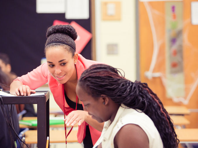 A Teach For America corps member working with a student at her desk.