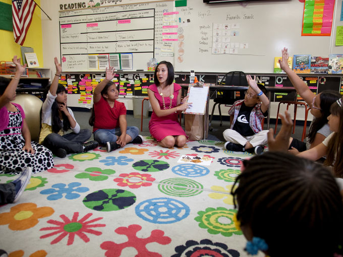 Corps member reads on carpet in Golfarb Elementary school.