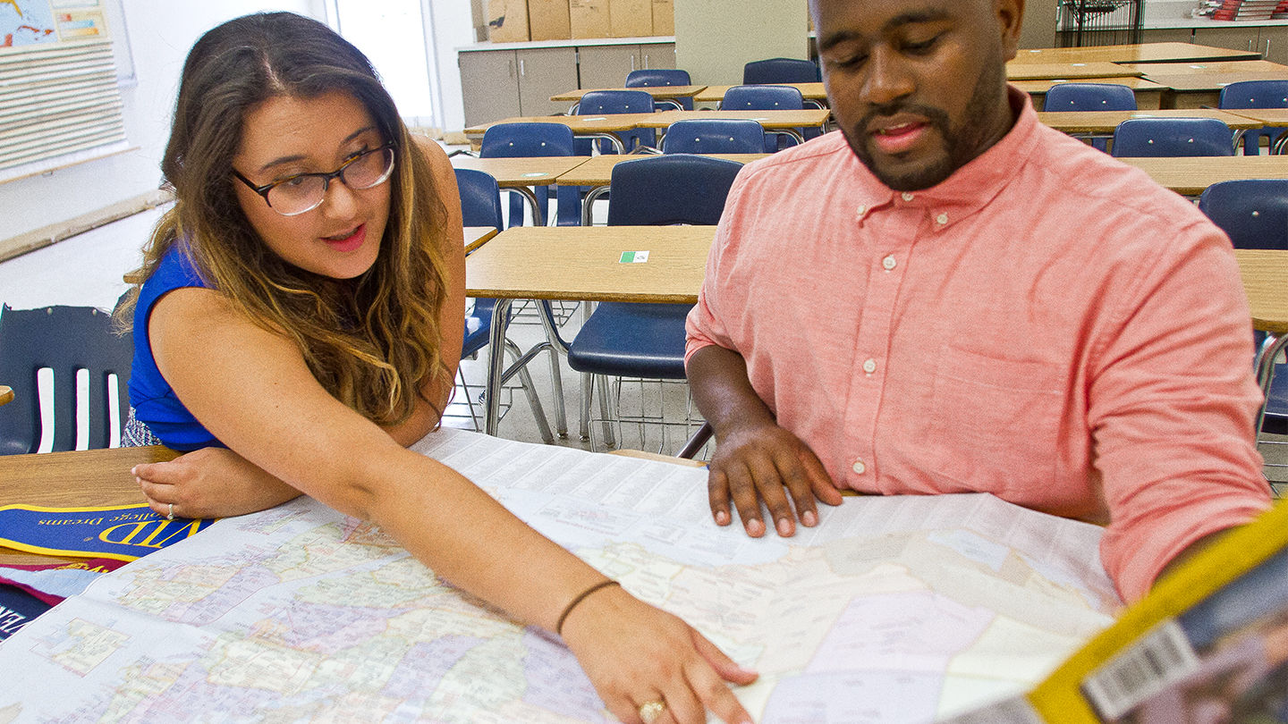 Two educators looking at a map