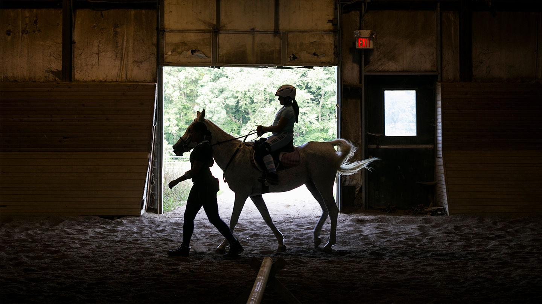 A young camper riding a horse
