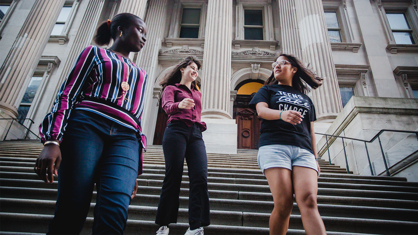 An image of three students in front of the New York City Department of Education building.