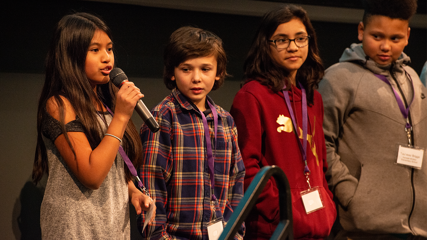 Four students standing on stage.