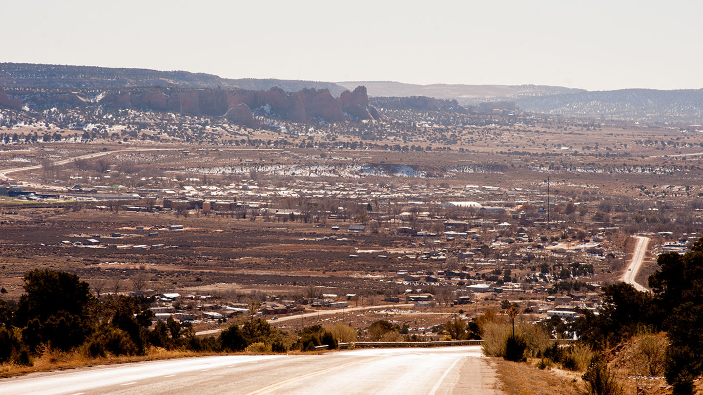 A panoramic photo taken at the top of a mountain on a highway overlooking a city; many more mountains are visible in the background.