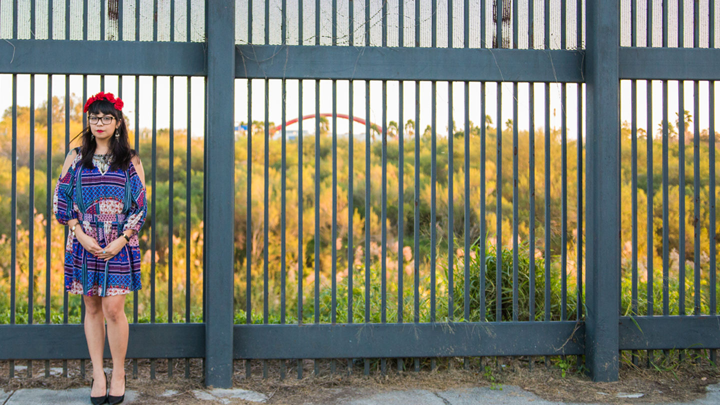 A woman in front of fence