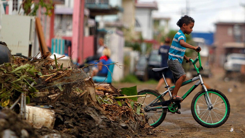 A young boy rides his bicycle through Puerto Rico.