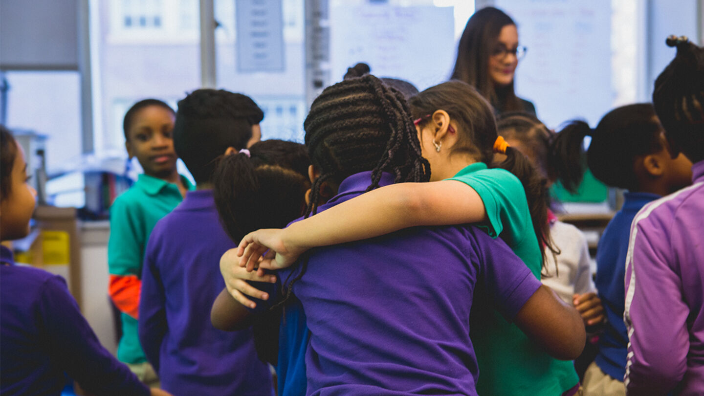 Students hug while in class.