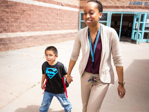 A Teach For America corps member holds a young student's hand while walking across school grounds.