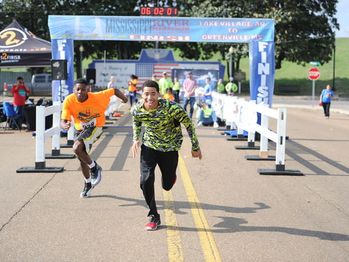 A young boy crosses the finish line in a marathon.