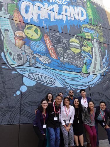 "Members of the Asian American Pacific Islander Initiative posing for a group photo near ""Visit Oakland"" street art."