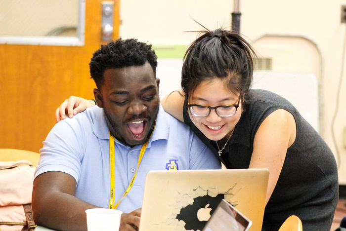 A Teach for America teacher working with a student at a computer.