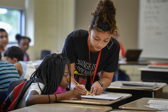 A Teach For America corps member working with a young student at her desk.