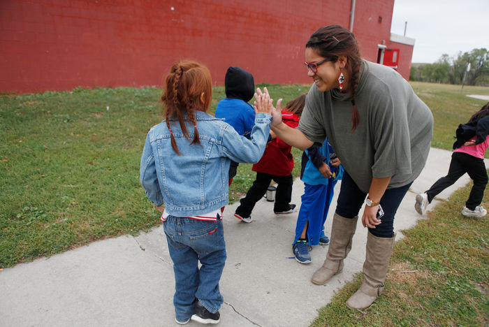 Mia Francis high fives students walking into South Dakota school.