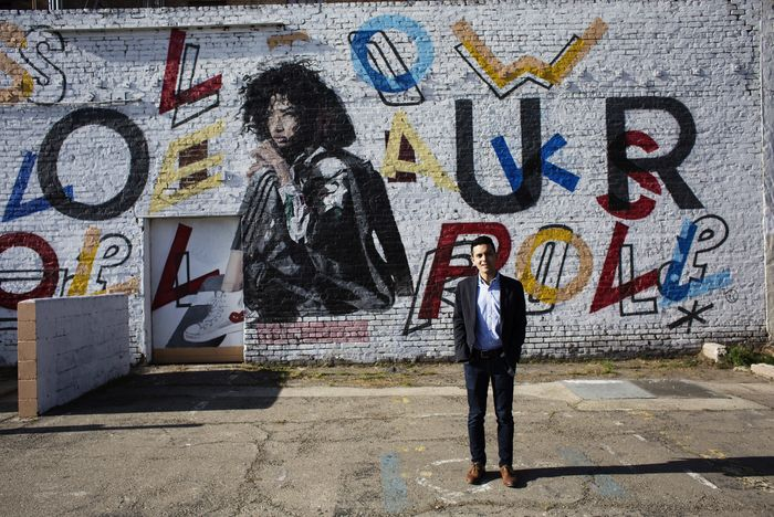 A TFA alumnus stands against a wall mural in Stockton, CA.