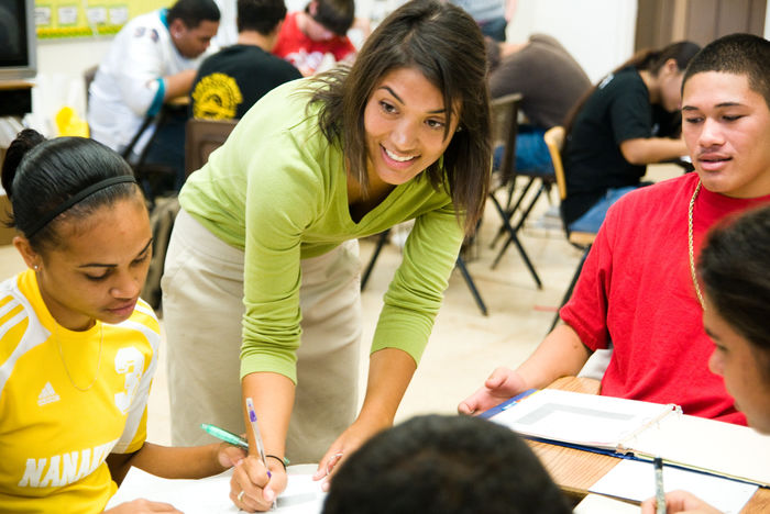 Corps member working with students in classroom.