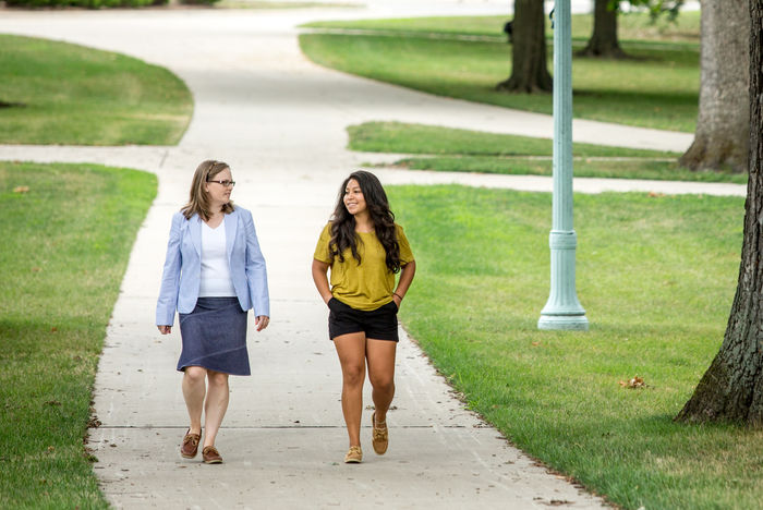 Two TFA corps members walk down a path together.