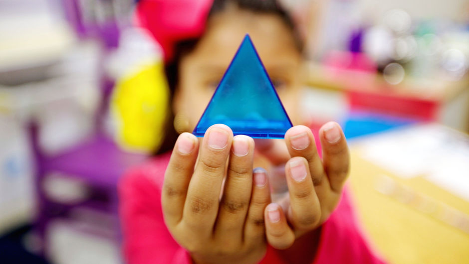 A young student holding a small clear blue pyramid.