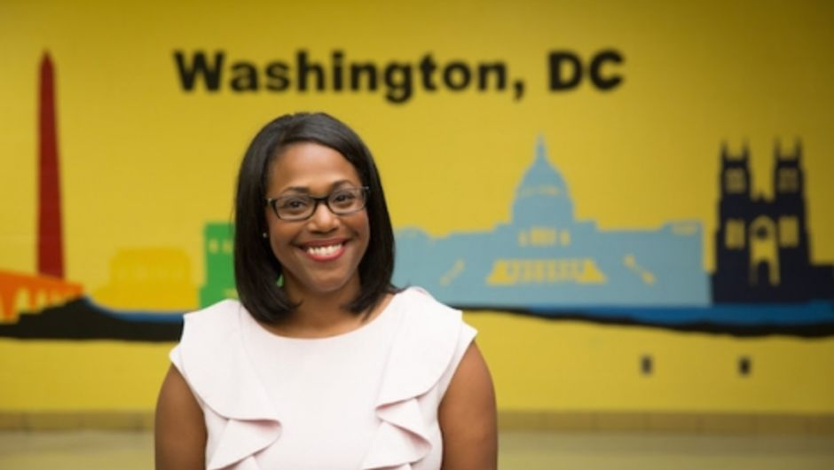 A Teach For America alumna standing in front of a school mural in a Washington, DC school.