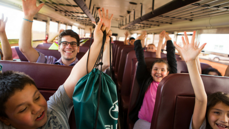 A Teach For America teacher riding on a bus with his students.