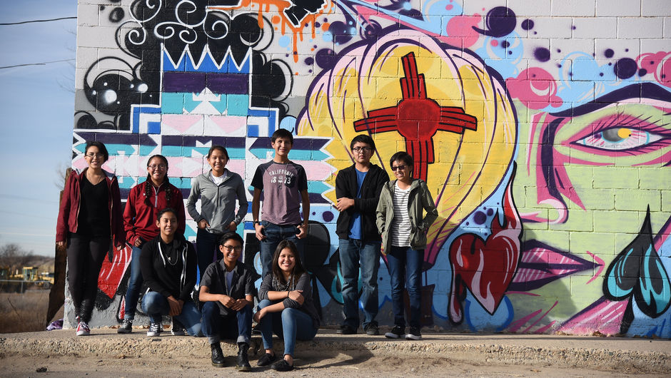 The Coding Club from Shiprock High School in front of a mural.