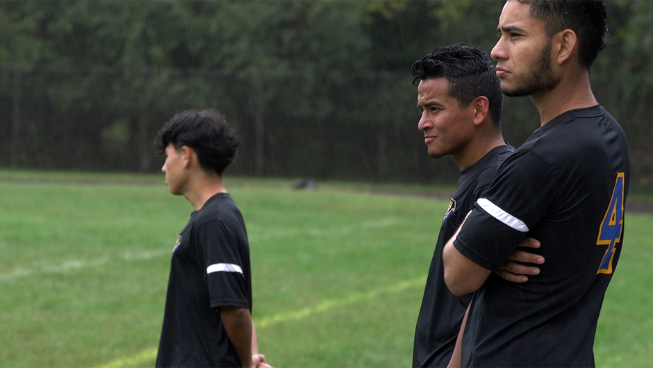 Three boys stand on the sideline as they watch their teammates play in a soccer game.