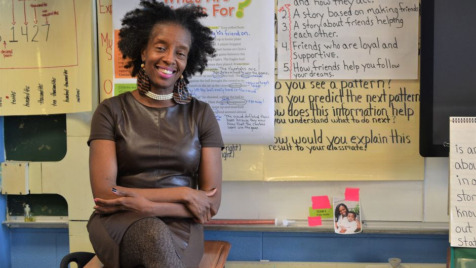 A TFA alum sits in her classroom, smiling