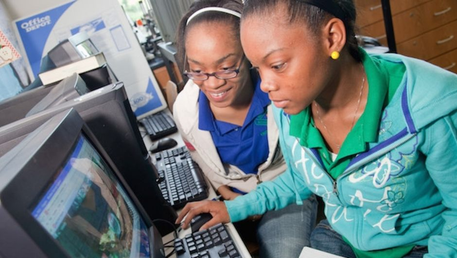 Two young Black girls work together at a computer.