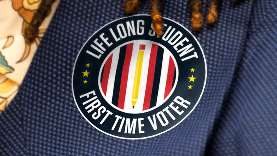 "A student wears a sticker that says ""Life Long Student, First Time Voter."""