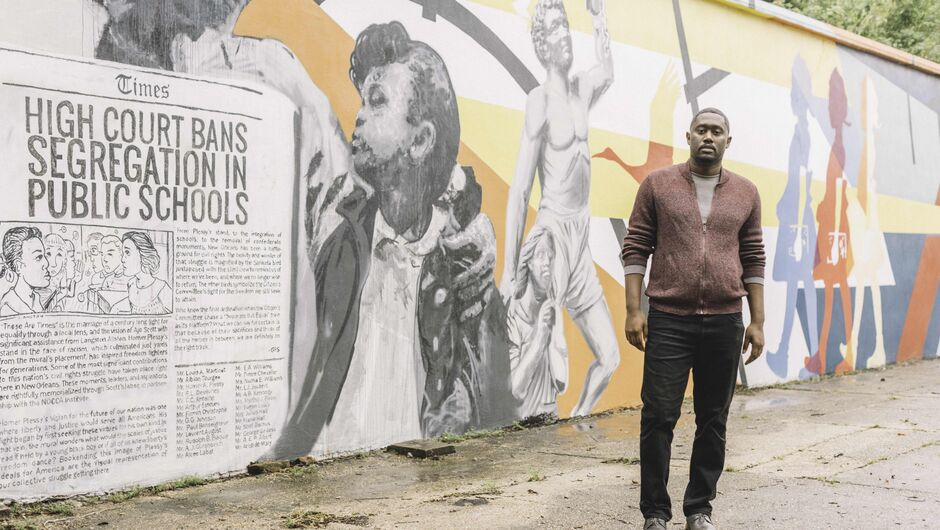 Bryan C. Lee Jr. stands in front of a portion of a mural in which  a newspaper is painted announcing the end of segregation in schools