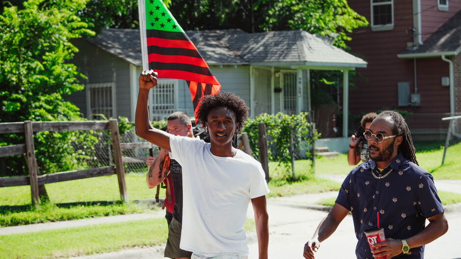 During the Juneteenth march in South Dallas a marcher raises his fist as the African American flag using the Pan-African colors wave.