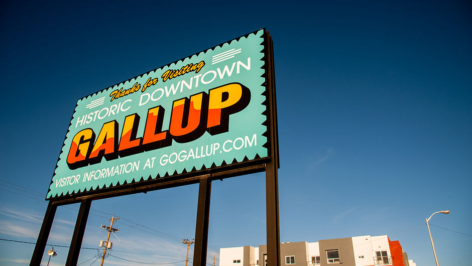 "A large bright blue sign that read, ""Thanks for visiting historic downtown Gallup. Visitor information at GoGallup.com."" In the background are the tops of houses, telephone polls, and large blue sky."