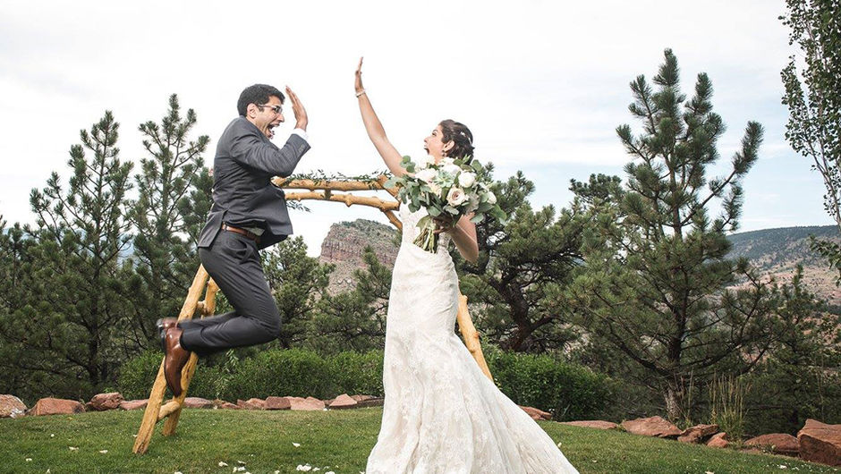 A man in a wedding suit jumping in the air and simultaneously high-fiving his bride.