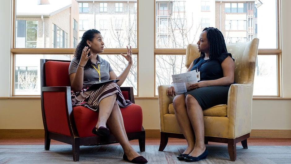 Two women talking in front of a window.