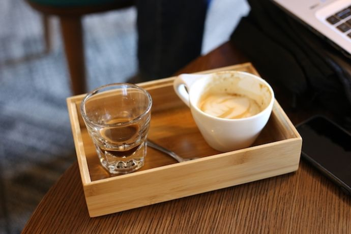 A cup of coffee in a tray at a coffee shop.