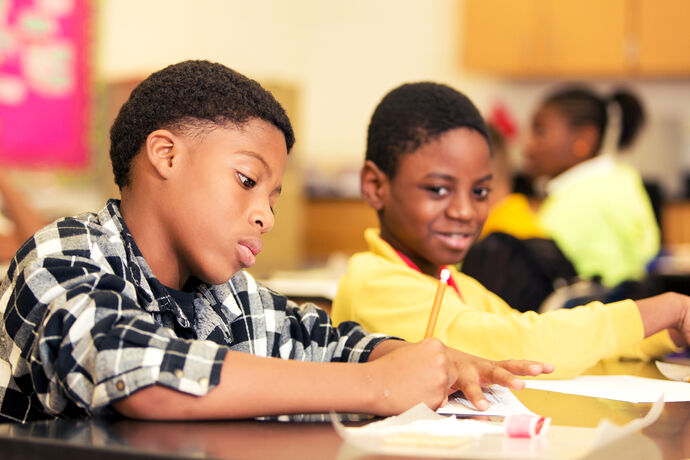 Two young students are sitting at desks in the classroom. One is looking at his paper while he writes on it, while the other boy is a little behind him is smiling looking over at his peer's paper.