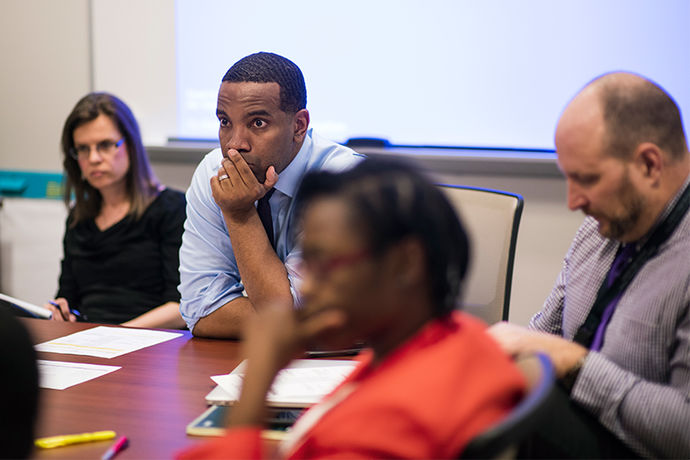David Hardy listens attentively to his colleagues during a meeting.