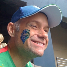 A middle-aged man with gray sideburns smiling while enjoying a sports game, wearing a blue baseball cap, a green sports shirt, and with a blue temporary tattoo of a team logo on his right cheek.