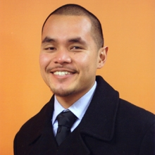 A young man with buzzed black hair and a thin mustache smiling in front of an orange background, wearing a black wool pea coat, a white dress shirt, and a dark blue tie.