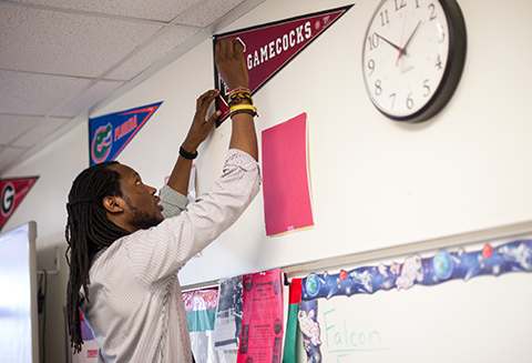 A young African-American male teacher tapes college pennants to the wall of his classroom.