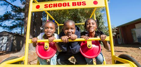 Three elementary students in a playground school bus frame structure, smiling.